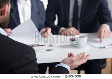 Close-up of man gesticulating during talk with future employers in corporation