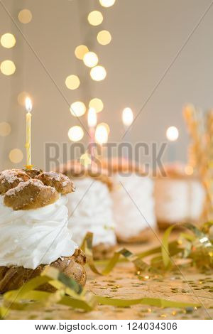 Row of sweet delicious fresh puffs with cream and candles on top
