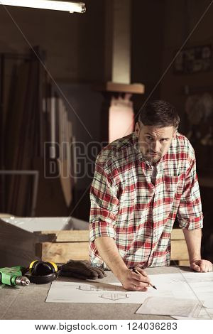 Carpenter correcting project lying on workbench in workshop.