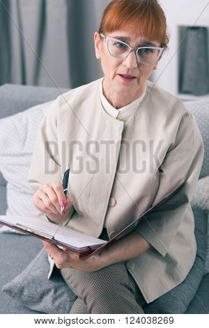 Senior wise marriage psychotherapist writing down her observations about couple