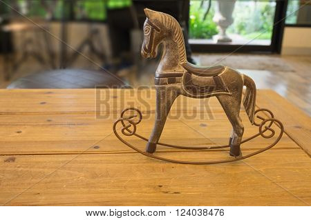Craving wooden horse toy on wooden table in evening with garden view from window / Craving wooden horse toy