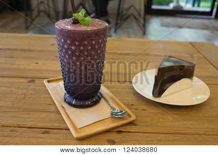 Fresh and healthy blueberry smoothie frappe in glass and wooden tray and table with chocolate fudge cake in evening / Fresh and healthy blueberry smoothie frappe and chocolate fudge