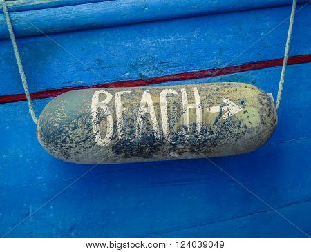 Retro Rustic Sign For A Beach On A Buoy On Of An Old Blue Boat