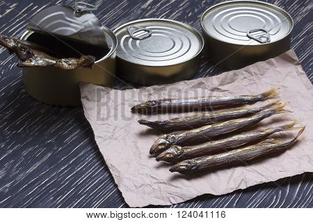 Smoked capelin and conserve tins on dark wooden background