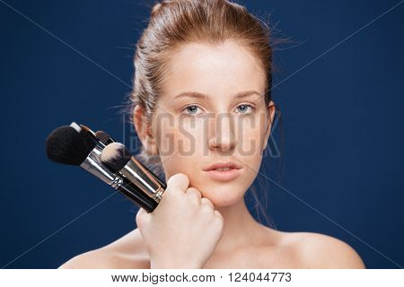 Beauty portrait of a young woman holding makeup brushes over blue background