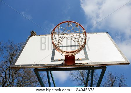 Picture of a basketball field goal with the sky in background.