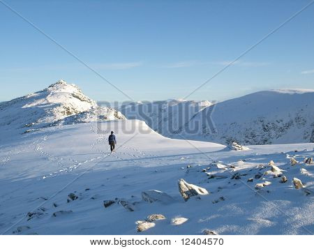 lone walker approaching top of dow crag english lake district in winter