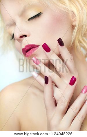 Burgundy multi-colored manicure and makeup on the blonde girl.