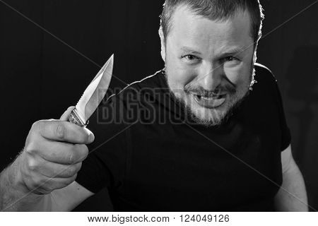 Portrait of a gangster with a knife low key