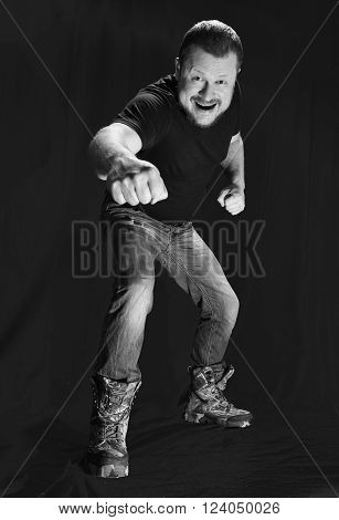 Emotional portrait of agressive bully fighting on black background