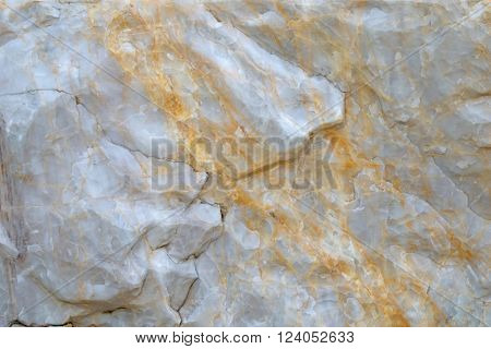 Closeup abstract background texture photo of white marble stone with oxidized iron stain pattern and cracks