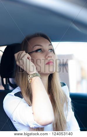 Woman putting make up in a car. Pretty young woman looking in mirror. Detail of woman face. Dangerous situation.