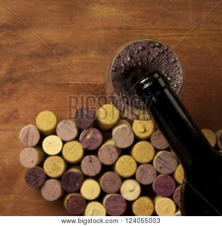Red wine poured from a bottle on a blurred background of many different wine corks and wooden boards