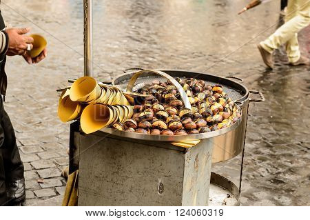 Roast chestnut vendor in the street during the autumn and the arrival of winter.