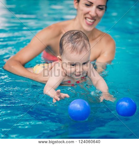 Cute baby boy swimming with his mother in the pool. Baby is trying to catch ball
