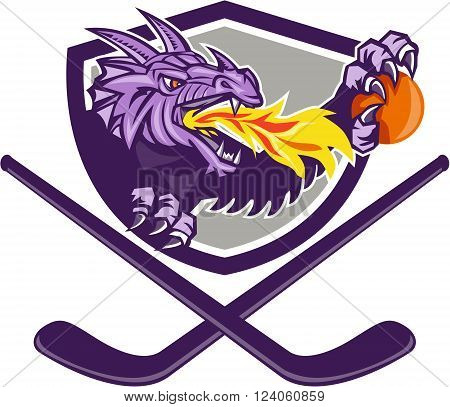 Illustration of a purple dragon head breathing fire clutching an ornage ball with crossed hockey stick set inside shield on isolated white background done in retro style.
