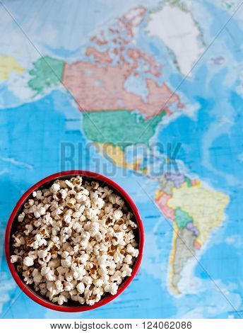 A big bowl of a warm homemade popcorn over a colorful world map.