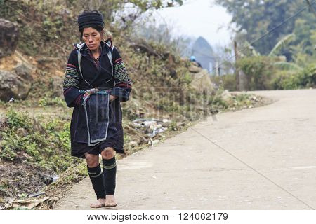 Sapa Vietnam - February 16 2016: Aboriginal woman of the mountains of Sapa in north Vietnam dressed with the traditional attire walking to her village