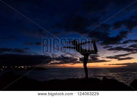 Summer sunset yoga session on beautiful Playa Fanabe beach - tropical Tenerife island, Canary in Spain. Warrior pose - Virabhadrasana