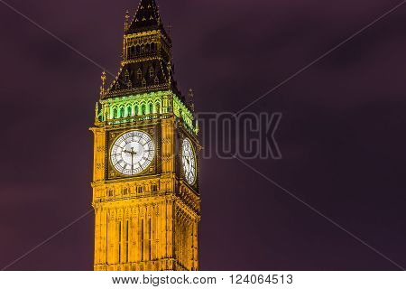 Elizabeth Tower's clock and Big Ben by night on a purple sky.