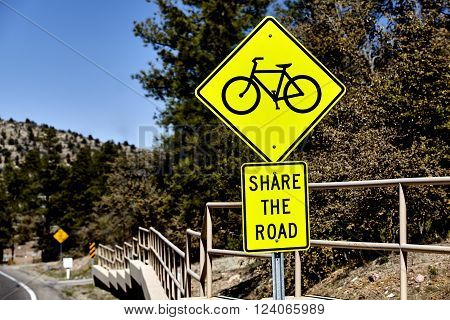 Yellow triangle road sign with a bicycle symbol indicating to motorist to share the road with bicyclist