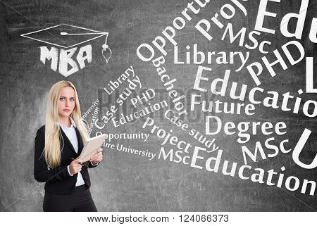 Young businesswoman with notebook education words flying from it. Black background. Concept of business studying.