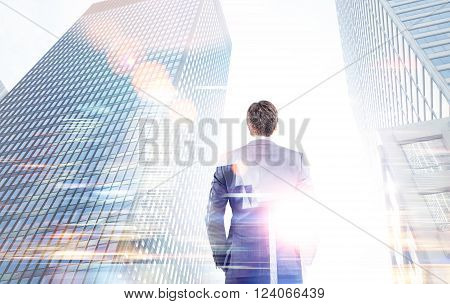 Businessman with hands in pockets between two skyscrapers. Double exposure. Concept of work.