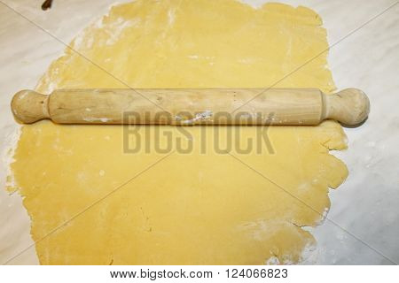 wooden old rolling pin rolling out dough