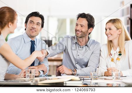 Business people shaking hands on finishing a meeting. Young businesswoman and businessman shaking hands during a meeting. Group of businesspeople welcoming a new trainee in the office.