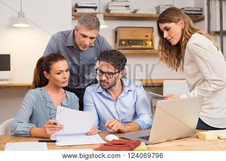 Business team discussing on document and idea at meeting. Businesspeople looking at past history of a company for merger. Meeting in office between creative people, casual business.