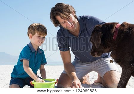 Cute little boy playing with sand. Happy father and son smiling and looking their labrador at beach. Father and son playing at beach with their brown dog.