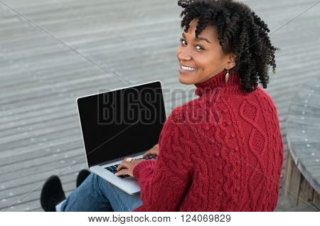 Young african woman sitting on wooden stairs outdoor and working on laptop. Happy casual woman sitting on wooden floors with laptop and looking at camera. Smiling adult student studying on pc.