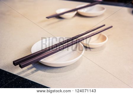 Empty dish with chopsticks on table. Asian dishware background.