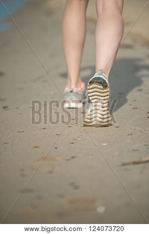Sport footwear, sand footprints and legs close up. Runner feet detail. Workout near ocean sea coast. Beautiful fit girl. Fitness model caucasian ethnicity outdoors. Weight loss exercise. Jogging.