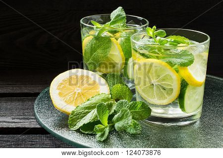 Fresh cold water with lemon cucumber ginger mint and ice in a glass on a glass tray
