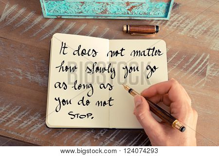 Retro effect and toned image of a woman hand writing on a notebook. Handwritten quote It does not matter how slowly you go as long as you do not stop as inspirational concept image