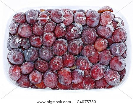 Fresh frozen fruits red plum in hoarfrost