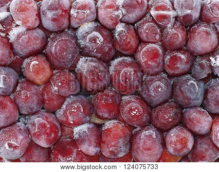 Backgrounds of fresh frozen fruits red plum in hoarfrost