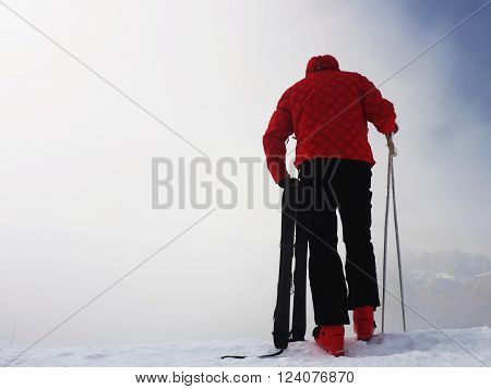 Skier in red winter jacket with small fun skis stay in snow in mountains. Fogy winter day at peak.