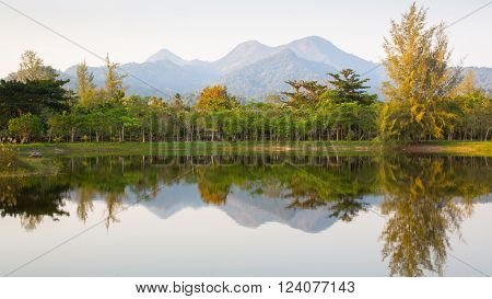 Panorama of mountains and forest reflected in the lake early in the morning, Thailand.