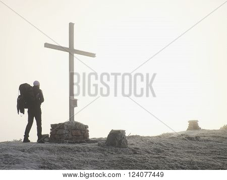 Tourist with big backpack stand at cross memorial on mountain peak. Man is watching into misty Alpine valley bellow. Metal cross at a mountain peak.