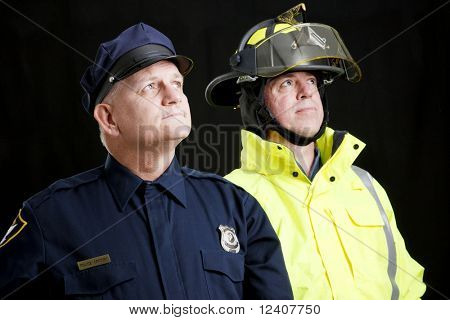 Reverent looking policeman and fireman photographed in front of a black background.