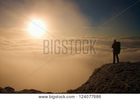 Tall hiker in black with gesture of triumph on view point. Heavy orange mist bellow in valley. Wonderful daybreak in mountains.