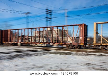 A blurred view of an empty railway flatcar racing across railway tracks.