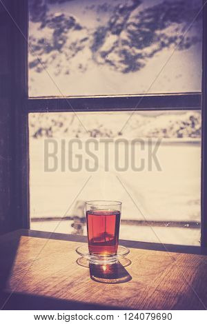 Retro old film style glass of hot tea on wooden table by a mountain shelter window cosiness and comfort concept shallow depth of field.