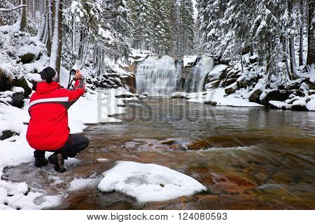 Photograph in red jacket with digital camera in hands is taking photo of winter frozen waterfall