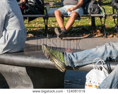 Manhattan New York - December 06 2015: People sitting and laying on the benches during lazy Sunday afternoon in Washington Square Park.