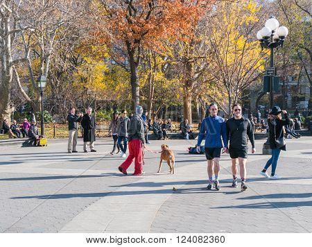 Manhattan New York - December 06 2015: People relaxing during lazy Sunday afternoon in Washington Square Park.