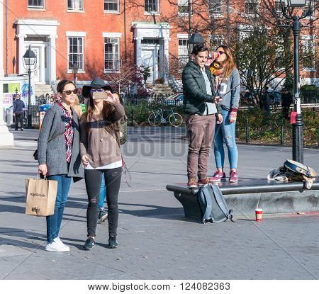 Manhattan New York - December 06 2015: People making selfies during lazy Sunday afternoon in Washington Square Park.