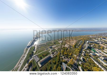 Aerial water power plant view with crossroads and roads, houses, buildings, parks and parking lots, bridges. Copter shot. Panoramic image.